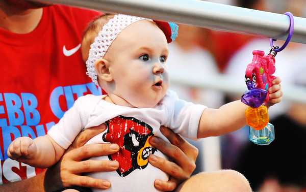 Globe/T. Rob Brown<br /> Seven-month-old Webb City fan Natalie Newby takes a break between portions of the Webb City football jamboree Friday night, Aug. 24, 2013, to play with a toy. She sits on the lap of her father, Dakota Newby.