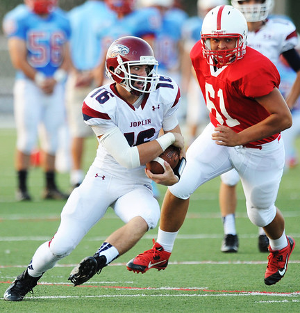 Globe/T. Rob Brown<br /> Joplin quarterback Skyler Duley maneuvers around Seneca defensive lineman Gabe Martin during Friday evening's jamboree, Aug. 23, 2013, at Webb City's field.