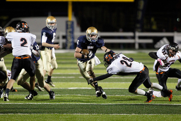Record-Eagle/Jan-Michael Stump<br /> Mancelona's Kevin Schepperley (28) tries to take down Traverse City St. Francis' Byron Bullough (5) in the first quarter of Friday's game.