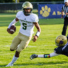 Record-Eagle/Brett A. Sommers Muskegon Catholic Central quarterback Cameron Martinez races by an outreaching Matt Loney during Friday's football game.