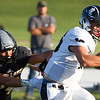 Record-Eagle/Brett A. Sommers New Lothrop quarterback Avery Moore breaks the tackle of Glen Lake's Jonathan Wright during Friday's football game. New Lothrop won 48-16.