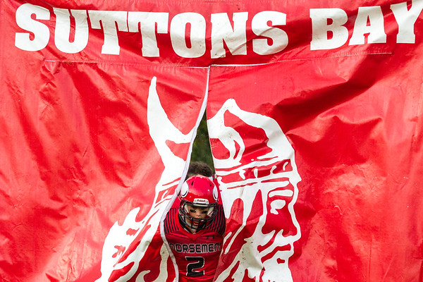Record-Eagle/Brett A. Sommers Suttons Bay quarterback Evan Rohrback runs through a school banner to enter the field before a football game against Onekama. Onekama won 54-18.