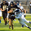 Record-Eagle/Brett A. Sommers Traverse City Central running back Dakota Cape-Perry attempts to break the tackle of Petoskey defender John Crittenden during Friday's 49-20 win over Petoskey.