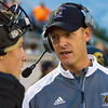 Record-Eagle/Brett A. Sommers Traverse City Central head coach Eric Schugars talks to Fitz Doud (2) on the sideline during Friday's 49-20 win over Petoskey.