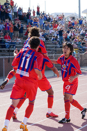 Val Teixeira mobbed by team-mates after scoring Palace's second goal.
