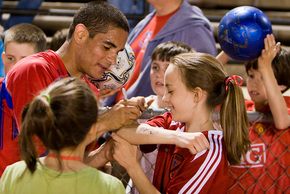 Carlos Morales signs a young fan's arm.