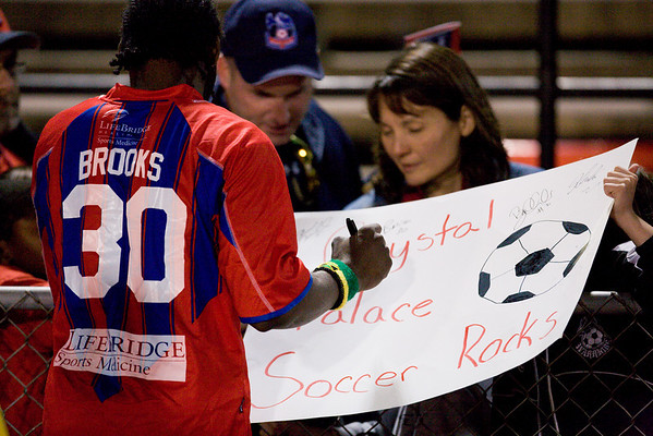 "Gary Brooks signs a giant ""Crystal Palace Soccer Rocks"" card."