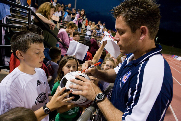 Co-Manager Pete Medd signs a soccer ball