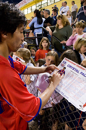 Shintaro Harada signs his photograph on the schedule poster