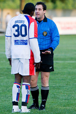 Gary Brooks gets a lecture from referee Niko Batsis (who would later send Brooks off)
