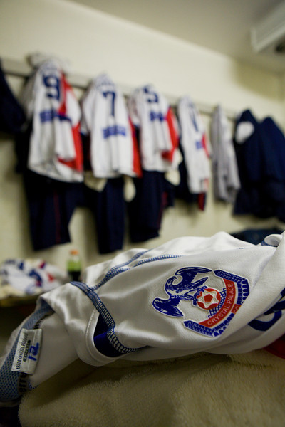 The visitors' locker room with Palace gear on the hooks