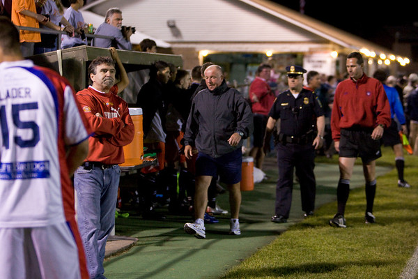 Pioneers' coach, Leszek Wrona, being escorted to the tunnel after being sent off by the ref