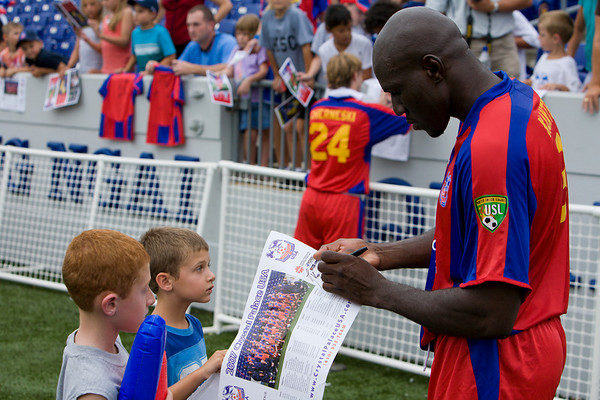 Ibrahim Kante autographs a team poster for a young fan