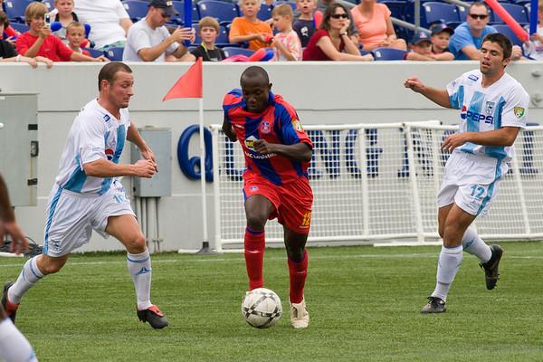 Matthew Mbuta dances his way past two Wilmington players