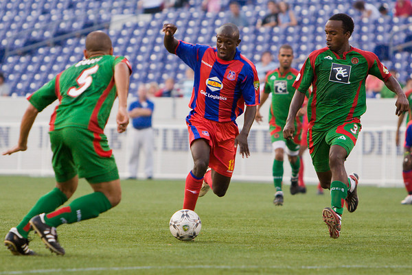 Matthew Mbuta splits two Bermuda defenders