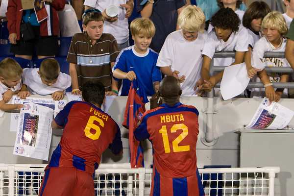 Rob Fucci and Matthew Mbuta sign autographs for a group of young supporters