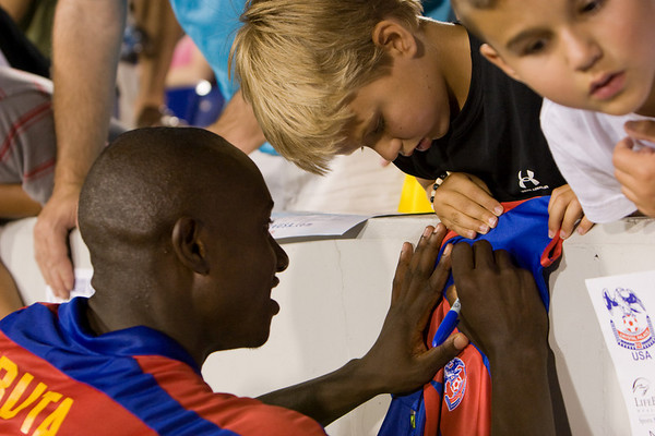 Matthew Mbuta autographs the replica jersey of a young Palace fan