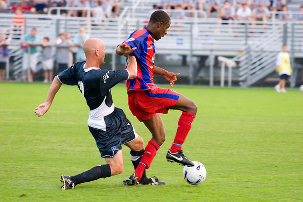 Veteran Todd Hicks challenges Arron Fray as he brings the ball up the pitch.
