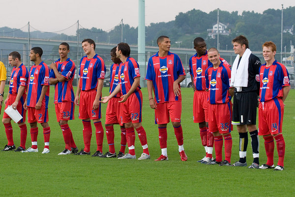 The first-half Palace UK team lines up to be introduced to the crowd.  Left to right:  Michael Huges, Jobi McAnuff, Lewis Grabban, Mark Hudson, Arron Fray, Marco Reich, Jay Bothroyd, Leon Cort, Rhoys Wiggins, Scott Flinders, Ben Watson.