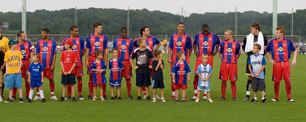 Palace UK's first-half team lines up with assorted kids after being introduced to the crowd.  Left to right:  Michael Huges, Jobi McAnuff, Lewis Grabban, Mark Hudson, Arron Fray, Marco Reich, Jay Bothroyd, Leon Cort, Rhoys Wiggins, Scott Flinders, Ben Watson.