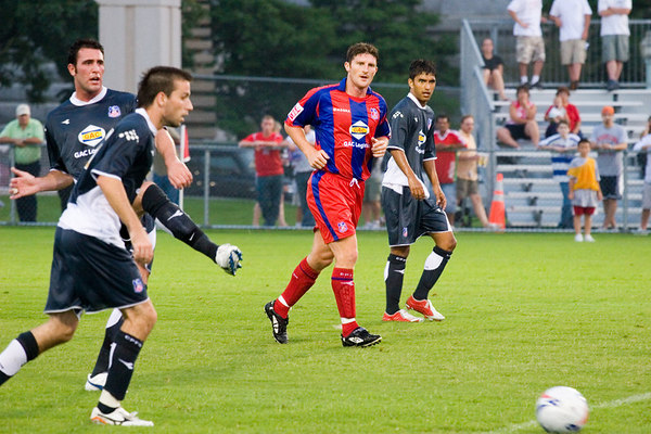 Marcus gross passes the ball out of the back as John Macken looks on.