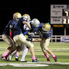 Record-Eagle/Keith King<br /> Saginaw Nouvel's Christopher Joynt is brought down by Traverse City St. Francis' Matt Seybert (82), from left, Daniel Gallagher (15), and Adam Armour (26), far right, Friday, October 5, 2012 at Thirlby Field in Traverse City.