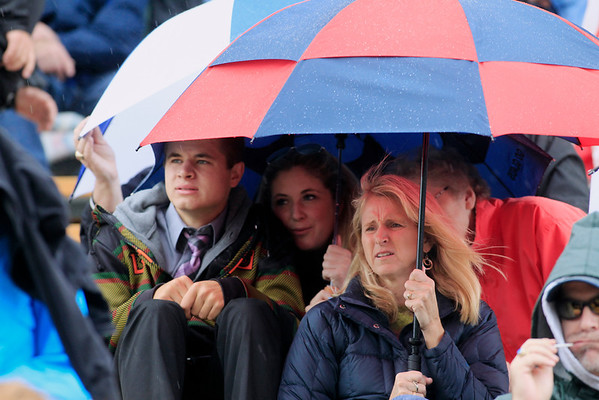 Record-Eagle/Jan-Michael Stump<br /> Fans attempt to stay dry during a downpour during Saturday's game between Boyne City and Traverse City St. Francis at Thirlby Field.