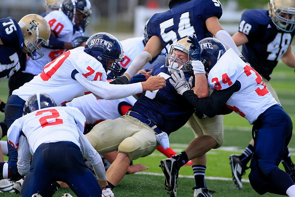 Record-Eagle/Jan-Michael Stump<br /> Boyne City's Michael Dohm (70) and Alan Manross (34) tackle Traverse City St. Francis' Byron Bullough (5) in the first quarter of Saturday's game.