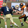 Record-Eagle/Jan-Michael Stump<br /> Traverse City St. Francis linebacker Gabe Gallagher (42) hurries Hudson quarterback Nathan Smith (10) in Saturday's state final in Detroit.