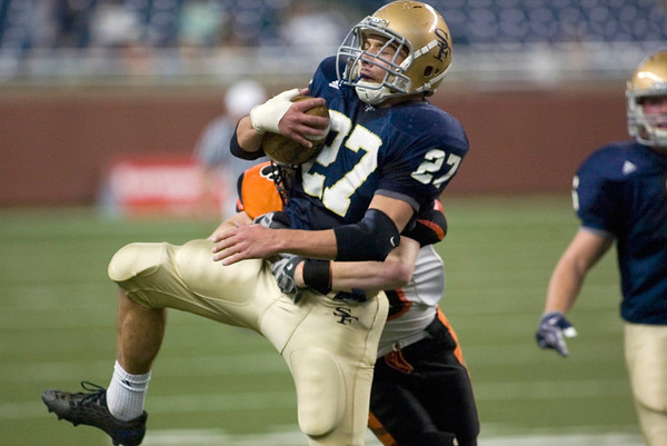 Record-Eagle/Jan-Michael Stump<br /> Traverse City St. Francis halfback John Zakrzewski (27) gets hit by Hudson linebacker Nathanial Osborne (36) in Saturday's state final in Detroit.