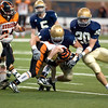 Record-Eagle/Jan-Michael Stump<br /> Traverse City St. Francis linebacker Max Bullough (44) and defensive back Matt Zakrzewski (20) tackle Hudson running back Drew Milligan (22) in the first quarter of Saturday's state final in Detroit.