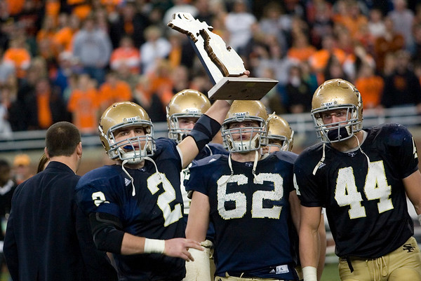 Record-Eagle/Jan-Michael Stump<br /> Traverse City St. Francis' Luke Popp (2), Angus MacLellan (62) and Max Bullough (44) hold up their state champion trophy after defeating Hudson 42-8 at Ford Field in Detroit.