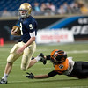 Record-Eagle/Jan-Michael Stump<br /> Traverse City St. Francis quarterback Riley Bullough (9) scrambles past outstretched Hudson linebacker Devan Marry (58) in Saturday's state final in Detroit.