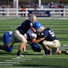 Record-Eagle/Keith King<br /> Ishpeming's Derek Slone is brought down by Traverse City St. Francis' Jack Brodeur, left, and Noah LaLonde Saturday, November 12, 2011 at Thirlby Field in Traverse City.
