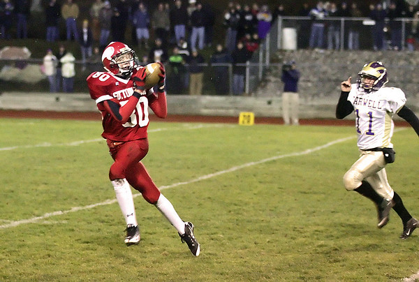 Record-Eagle/Keith King<br /> Suttons Bay's Nicolas Cross catches the ball prior to running for extra yards as Farwell's Cody Wilkerson pursues Friday, November 5, 2010 at Suttons Bay High School.