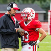 Record-Eagle/Brett A. Sommers Benzie Central coach Jason Katt relays the play call to Darren Childs during Friday's football game against Traverse City St. Francis.