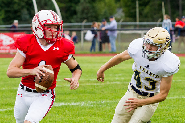 Record-Eagle/Brett A. Sommers Benzie Central quarterback Joe Wade runs from Traverse City St. Francis linebacker Andrew Simaz during Friday's football game.