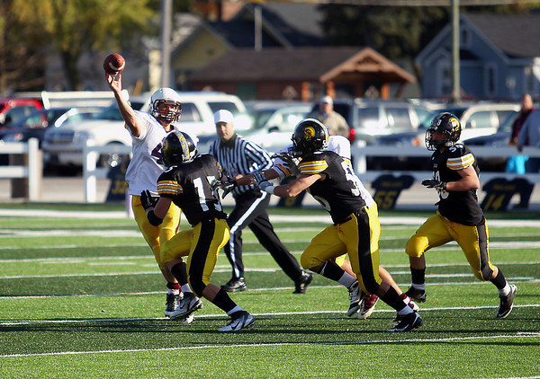 Record-Eagle/Keith King<br /> Menominee's Tanner Mccoux passes the ball as Traverse City Central's defense pursues Saturday, October 22, 2011 at Thirlby Field in Traverse City.