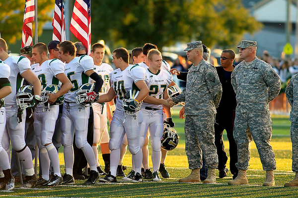 "Record-Eagle/Jan-Michael Stump<br /> Traverse City West players greet veterans during opening ""Patriot Game"" ceremonies before Friday's game against Traverse City Central."