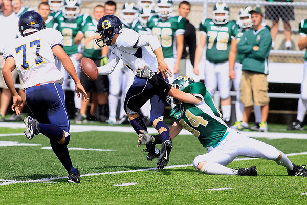 Record-Eagle/Jan-Michael Stump<br /> Gaylord quarterback Tyler Frisch (4) gets tackled by Traverse City West defensive end James Peck (84) Saturday at Thirlby Field.