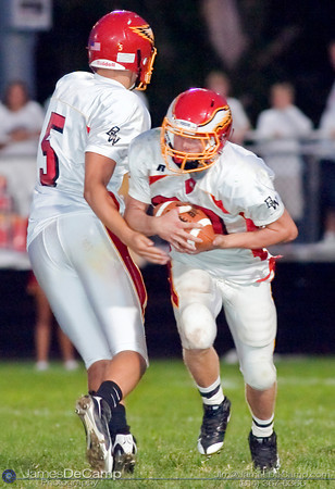 Big Walnut High School Quarterback #5 John Cannell hands off the ball to #20 Cody Leitner during the third quarter of play in the teams season opener held at Westerville Central High School Saturday evening August 29, 2009. The game was postponed Friday night and moved to Saturday afternoon due to violent weather.  (Photo by James D. DeCamp 614-367-6366)  http://www.JamesDeCamp.com