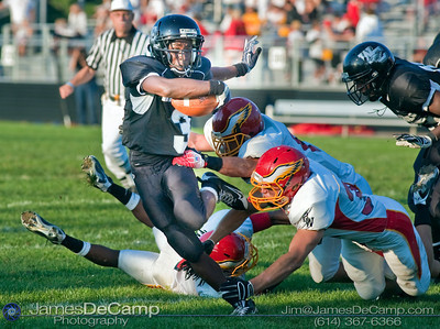 Westerville Central High School #3 John Howard slips through the Big Walnut High School defensive line in the second quarter of play in the teams season opener held at Westerville Central High School Saturday evening August 29, 2009. The game was postponed Friday night and moved to Saturday afternoon due to violent weather.  (Photo by James D. DeCamp 614-367-6366)  http://www.JamesDeCamp.com