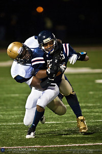 Bishop Hartley High School's Alonzo Saxton (21) is brought down by Akron Hoban Knights Greg Mullen (9) in the first quarter of play Friday night September 16, 2011 at Bishop Hartley High School.