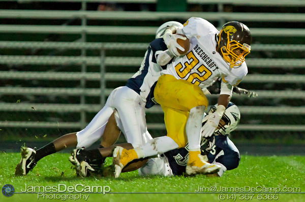 Beechcroft High School's Kevin Chapple (32) is brought down by Whetstone High School's Yusef Conteh (23), left, and Javon Henry (3) in the first quarter of play at Whetstone High School Friday night September 23, 2011.