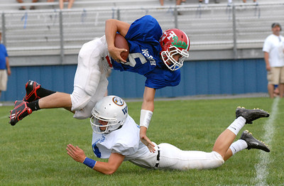 South's Tyler Pratt of Shikellamy tackles North's quarterback, Lucas Havens of Troy, during the District IV All-Star Football game in South Williamsport Friday June 29, 2012.