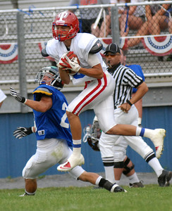 South's Jacob Kleman of Mount Carmel makes the catch over North's Clayton Good of Muncy during the District IV All-Star Football game in South Williamsport Friday June 29, 2012.