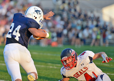 Amanda August/For The Daily Item Mifflinburg High School's Tyler Stolzfus (24) attempts to dodge Selinsgrove High School's Logan Benner (4) during the football game in Mifflinburg on Friday night. Selinsgrove won 3-0.