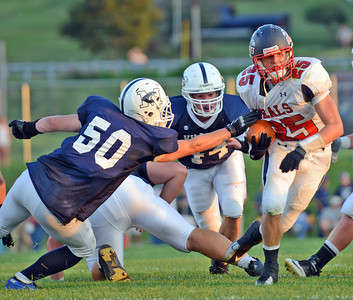 Amanda August/For The Daily Item Selinsgrove's Zach Adams (25) pushes through the Mifflinburg defense during the football game in Mifflinburg on Friday night. Selinsgrove won 3-0.