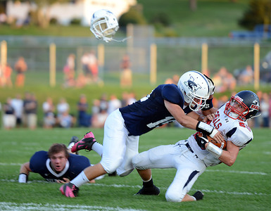 Amanda August/For The Daily Item Mifflinburg High School's John Punako (15) tackles Selinsgrove High School's Zach Adams (25) on Friday night.