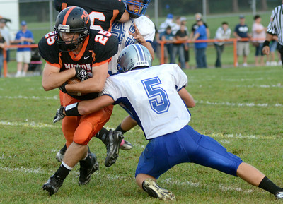 Milton's Jarred Fogelman hangs on to the ball as Warrior Run's Kaelen Fausey brings him down during their game Friday Sept. 7, 2012 in Milton.